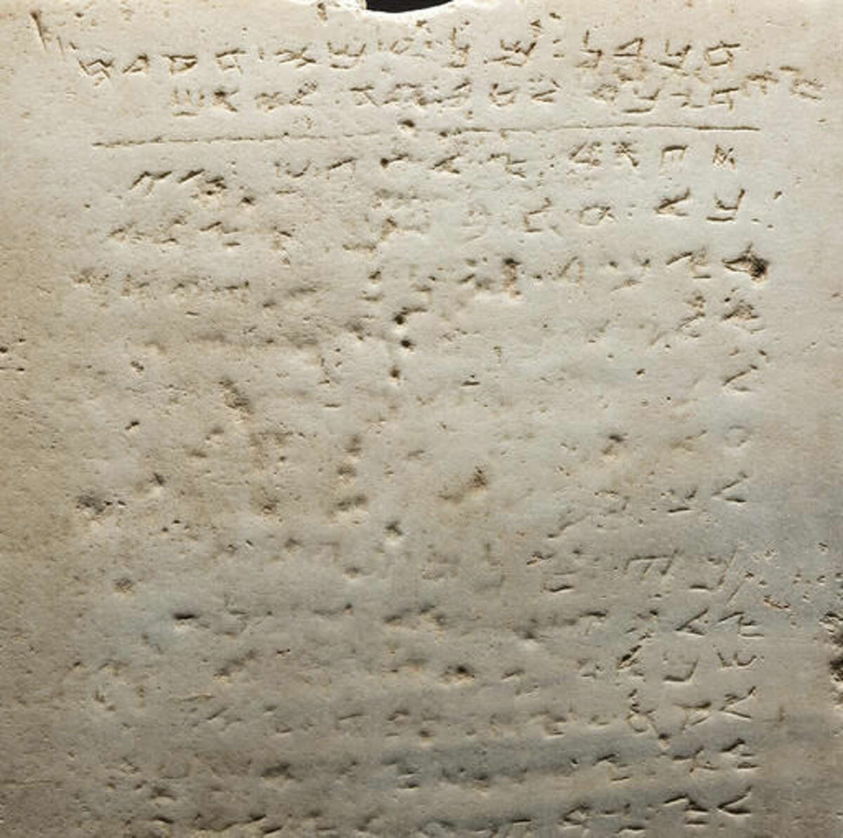This undated photo provided by Heritage Auctions, HA.com shows the world's earliest-known stone inscription of the Ten Commandments - a two-foot square slab of white marble, weighing about 115 pounds and inscribed in an early Hebrew script called Samaritan, that sold for $850,000 Wednesday evening, Nov. 16, 2016, at a public auction of ancient Biblical archaeology artifacts held by Heritage Auctions in Beverly Hills, Calif. (Matt Roppolo/Heritage Auctions, HA.com via AP)