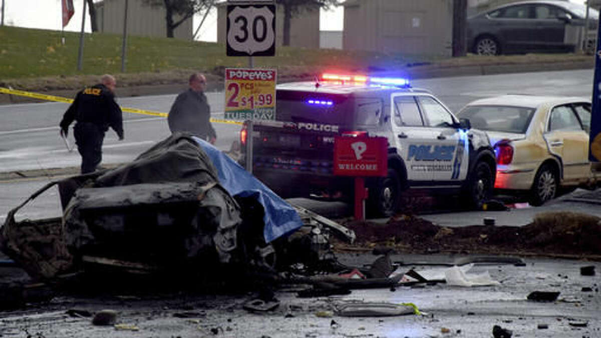 Police investigate the scene of a multi-vehicle crash at the intersection of Route 30 and Route 48, Thursday, Nov. 24, 2016, in North Versailles, Pa. Police say a man who led them on a car chase and caused a fiery crash that killed three people near Pittsburgh had been wanted in a drug case. East McKeesport police Chief Russell Stroschein says the driver headed into North Versailles, ran a red light and hit two cars, killing three people in one of them. (Darrell Sapp/Pittsburgh Post-Gazette via AP)