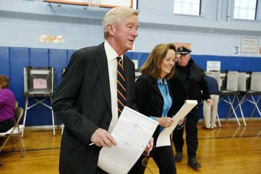 Libertarian vice presidential candidate, former Massachusetts Gov. Bill Weld. and his wife Leslie Marshall, hold ballots before casting their votes at the John F. Kennedy Elementary School in Canton, Mass., Tuesday, Nov. 8, 2016. (AP Photo/Michael Dwyer)