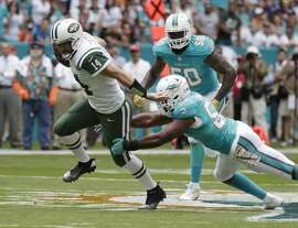 New York Jets quarterback Ryan Fitzpatrick (14) runs away from a tackle by Miami Dolphins outside linebacker Jelani Jenkins (53), during the first half of an NFL football game, Sunday, Nov. 6, 2016, in Miami Gardens, Fla. To the right is Miami Dolphins defensive end Andre Branch (50). (AP Photo/Lynne Sladky)
