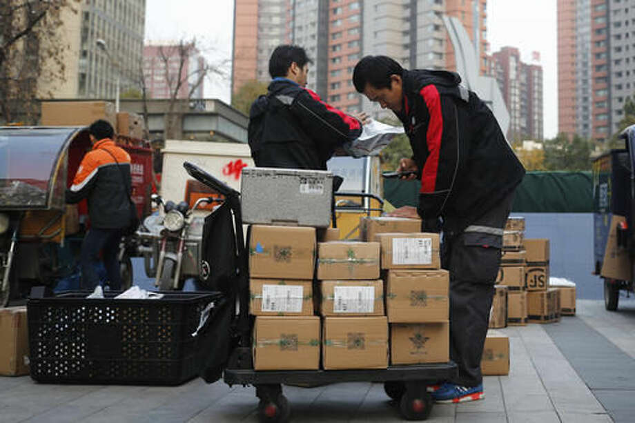 Delivery workers sort parcels for their customers in Beijing. Photo: Andy Wong