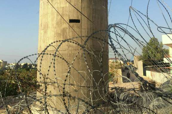 """A picture taken on November 21, 2016 shows a building structure at the Palestinian Ain al-Hilweh refugee camp, near the Lebanese southern coastal city of Sidon.  Lebanon is building a wall near the country's largest Palestinian refugee camp to prevent jihadist infiltrations, a military source said, as some denounced a """"wall of shame"""" like Israel's separation wall.    / AFP PHOTO / STRINGERSTRINGER/AFP/Getty Images"""
