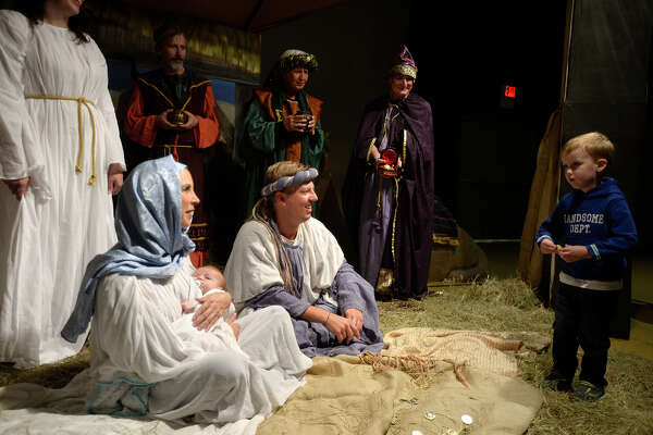 """Jackson Worthey, 3, gets a closer look at newborn Jesus during the """"Road to Bethlehem"""" live nativity scene at Wesley United Methodist Church on Monday evening. The event takes visitors on a journey through Bethlehem en route to the stable scene where Jesus was born.  Photo taken Monday 12/5/16 Ryan Pelham/The Enterprise"""