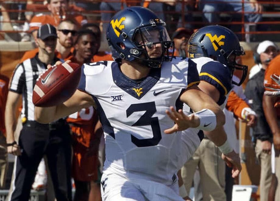 West Virgina quarterback Skyler Howard looks to throw during the first half of an NCAA college football game against Texas, Saturday, Nov. 12, 2016, in Austin, Texas. (AP Photo/Michael Thomas)