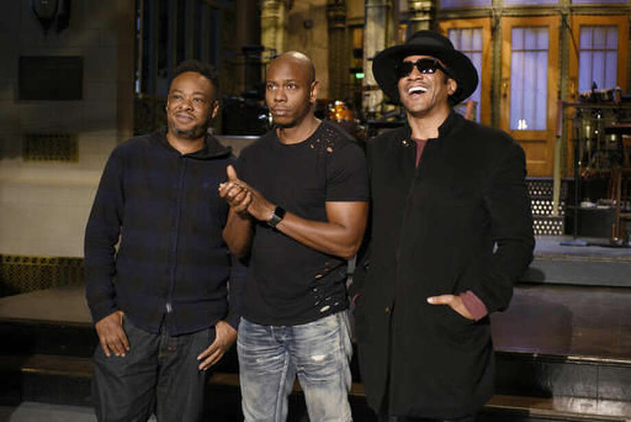 "In this Nov. 10, 2016 photo released by NBC, Jarobi White and Q-Tip of musical guest A Tribe Called Quest pose with host Dave Chappelle, center, on the television show, ""Saturday Night Live,"" in New York. ""Saturday Night Live"" called on host Chappelle's wit for a thoughtful coda to a divisive presidential campaign. Chappelle offered an African-American take on President-elect, Donald Trump's victory over Hillary Clinton, saying he hadn't seen white people so mad since the O.J. Simpson verdict. (Rosalind O'Connor/NBC via AP)"