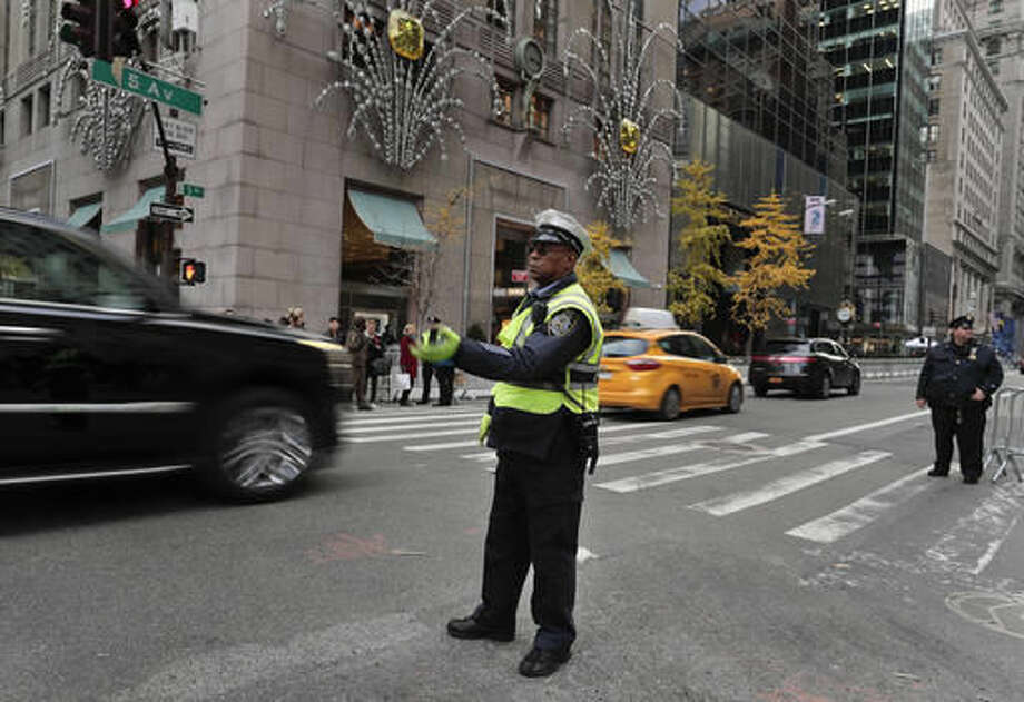 A New York police officer directs traffic along Fifth Avenue where lanes were closed in front of Trump Tower where President-elect Donald Trump continued meetings with members of his transition team, Wednesday, Nov. 16, 2016, in New York. (AP Photo/Julie Jacobson)