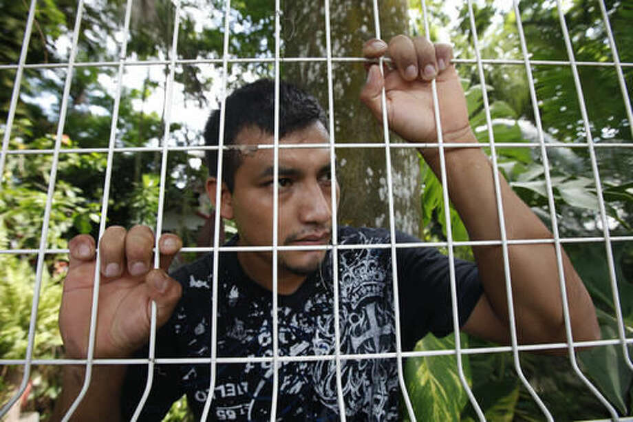 """In this July 2, 2016 photo, the gardener for human rights acticists Juan Carlos Soni Bulos, Luis Enrique Biu Gonzalez, talks through the fence of Soni's house in Tanquian de Escobedo, San Luis Potosi, Mexico. Biu, who was also taken and tortured by Mexican Marines, recalls the marines giving them electric shocks, especially when they got to Soni. """"Now we're going to give it to fatty to see if he can take it,"""" one marine said in reference to Soni. (AP Photo/Marco Ugarte)"""