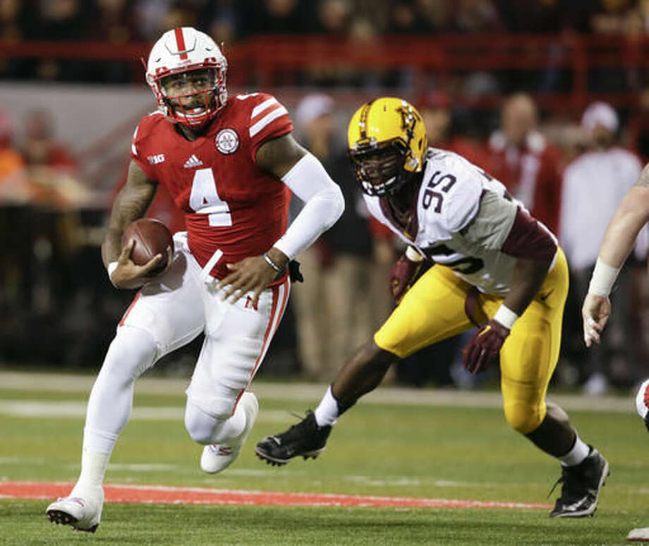 Nebraska quarterback Tommy Armstrong Jr. (4) runs away from Minnesota defensive lineman Hendrick Ekpe (95) during the first half of an NCAA college football game in Lincoln, Neb., Saturday, Nov. 12, 2016. (AP Photo/Nati Harnik)