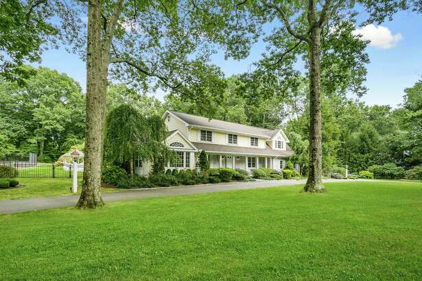 The whited washed brick and buttercream yellow colonial house at 330 11 O'clock Road is in the northern end of Fairfield and has a semi circular driveway.