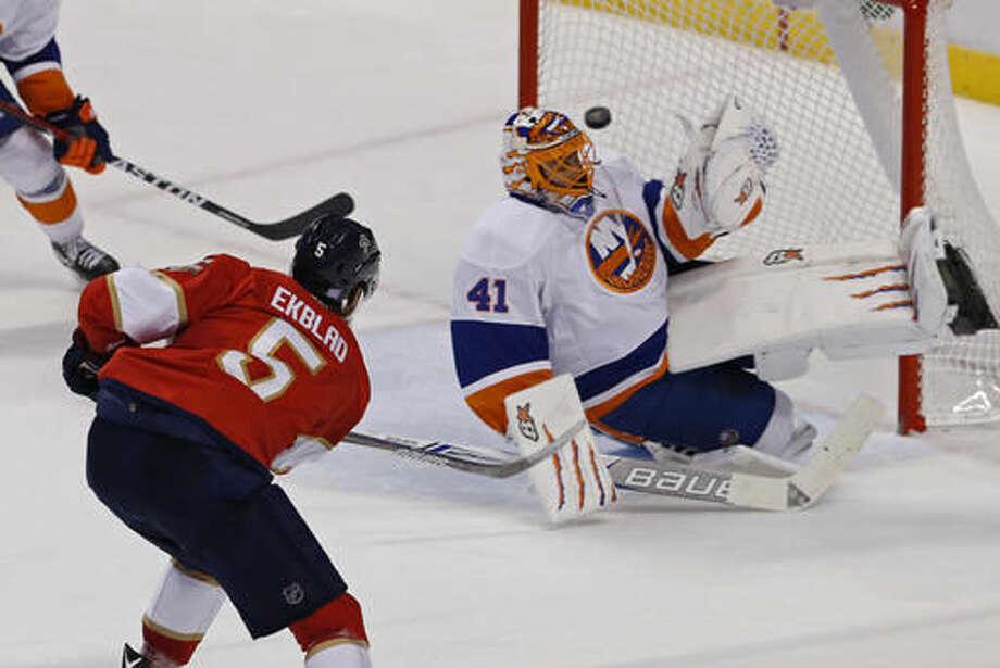 Florida Panthers defenseman Aaron Ekblad (5) has his shot deflected by New York Islanders goalie Jaroslav Halak (41) in the second period of an NHL hockey game, Saturday, Nov. 12, 2016, in Sunrise, Fla. (AP Photo/Joe Skipper)