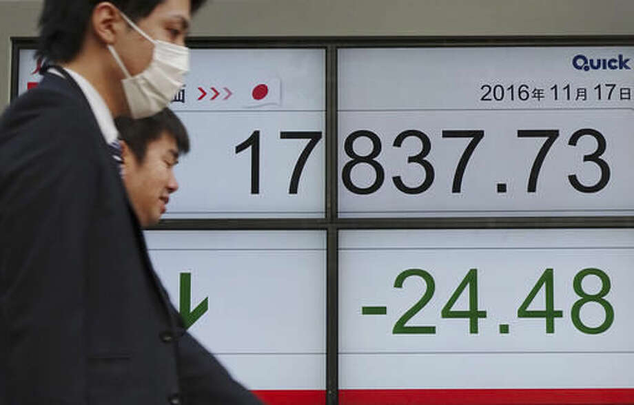 Men walk past an electronic stock board showing Japan's Nikkei 225 index at a securities firm in Tokyo, Thursday, Nov. 17, 2016. Asian stock markets were mixed Thursday as a seven-day rally on Wall Street petered out overnight. The U.S. dollar retreated slightly after hitting a 13-year high and oil prices slipped. (AP Photo/Eugene Hoshiko)