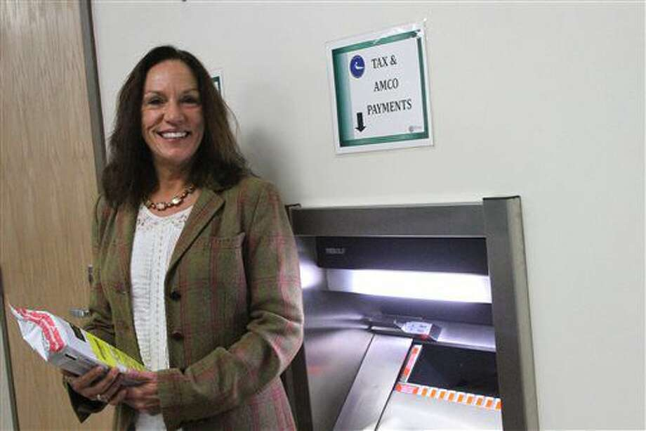 This photo taken Monday, Nov. 14, 2016, in downtown Anchorage, Alaska, shows Kelly Mazzei, revenue audit supervisor for the state of Alaska tax division, posing with a deposit safe intended for marijuana businesses to pay their taxes in cash. It's the only in-person drop-site for cash tax payments for marijuana businesses. Banking remains an issue for legal pot businesses in Alaska, since marijuana is still considered an illegal drug on the federal level. (AP Photo/Mark Thiessen)