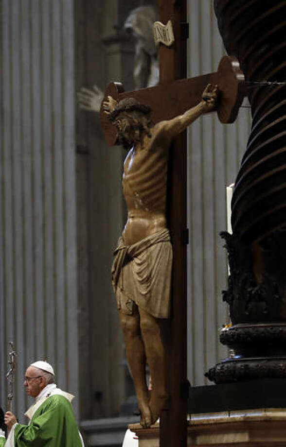 Pope Francis stands near a wooden crucifix as he celebrates a mass on the occasion of the homeless jubilee in St. Peter's Basilica, at the Vatican, Sunday, Nov. 13, 2016. (AP Photo/Gregorio Borgia)