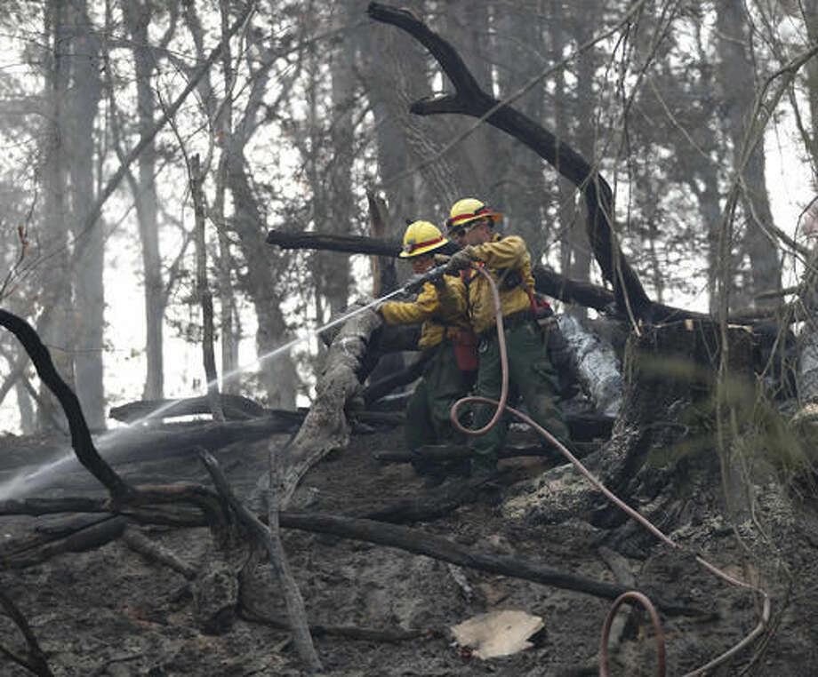 In this Tuesday, Nov. 15, 2016 photo, firefighters Valarie Lopez, left, and Mark Tabaez work to cool hot spots after a wildfire burned a hillside in Clayton, Ga. More than 5,000 firefighters and support personnel, including many veterans of wildfires in the arid West, and 24 helicopters are reinforcing local crews in the fire zone, which has spread from northern Georgia and eastern Tennessee into eastern Kentucky, the western Carolinas and parts of surrounding states.(AP Photo/John Bazemore)