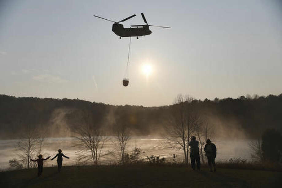 In this Tuesday, Nov. 15, 2016 photo, a Chinook pulls water out of Lake Oolenoy near Table Rock State Park in S.C., as firefighters continue to battle wildfires. (Heidi Heilbrunn/The Greenville News via AP)