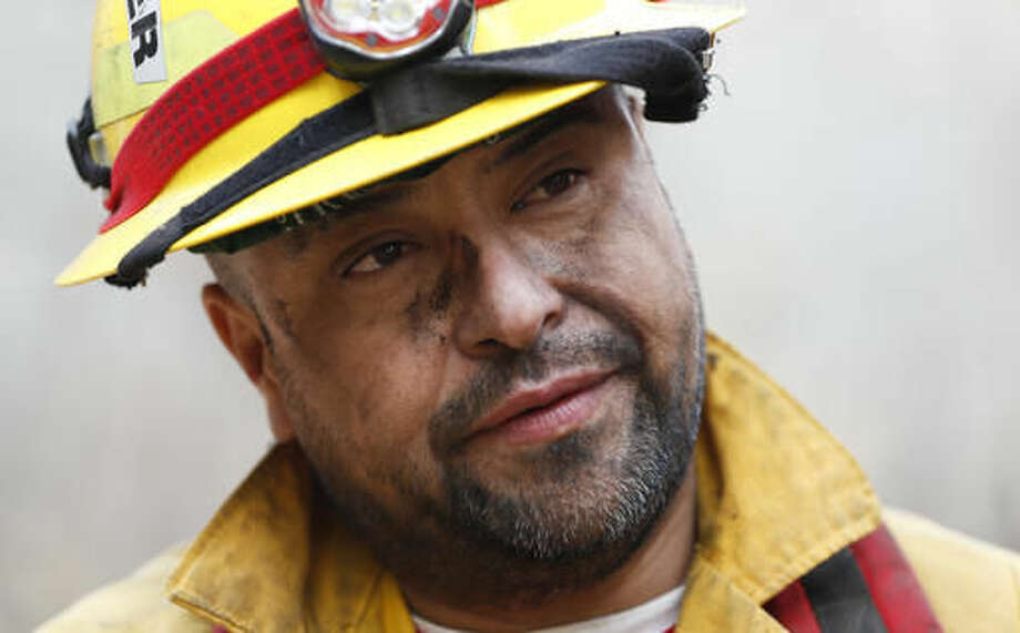 In this Tuesday, Nov. 15, 2016 photo, firefighter Mark Tabaez speaks with a reporter after battling a wildfire in Clayton, Ga. There were more than 30 uncontained large fires burning across the southeast, federal officials said in a Wednesday update. Fires across the region have burned a total of 128,000 acres, or about nine times the size of Manhattan.(AP Photo/John Bazemore)