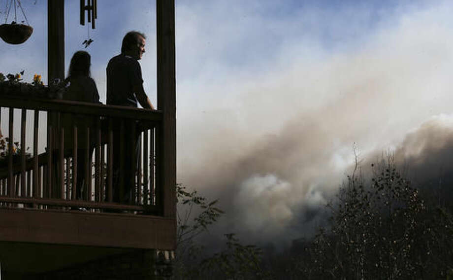 Eric and Vebbra Willey watch from their porch as the Rock Mountain wildfire approaches closer to their home on Wednesday, Nov. 16, 2016, in Tate City, Ga. Residents are under a pre-evacuation order as firefighters work to keep the fire away from homes. (Curtis Compton/Atlanta Journal-Constitution via AP)