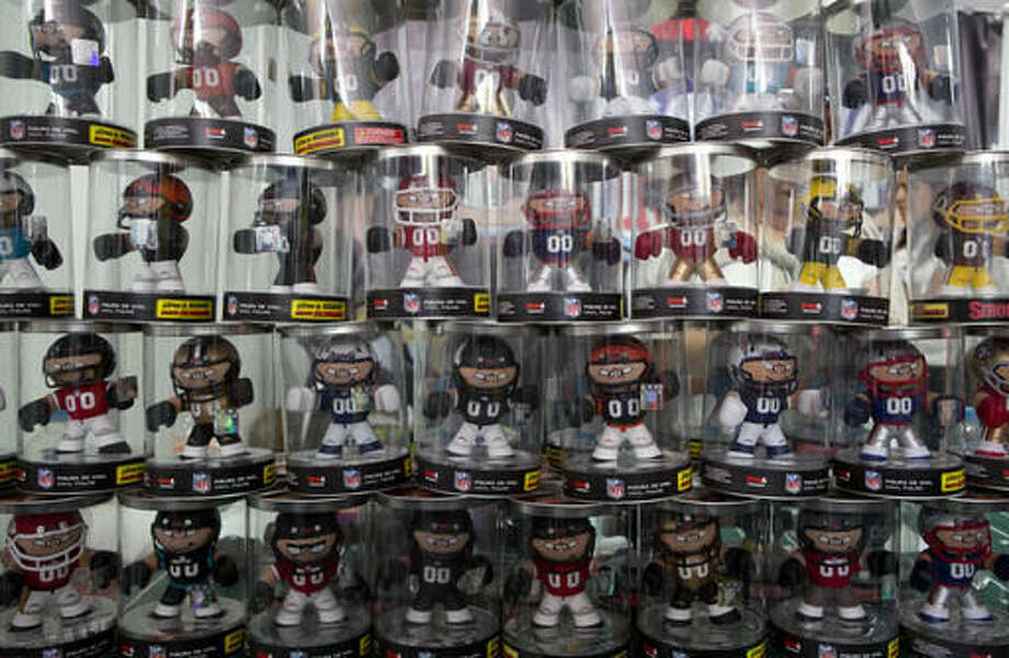 In this Nov. 6, 2016 photo, statuetes of players from American football teams stand for sale at the third annual American Football Expo in Mexico City. Local football historian Alejandro Morales, who also created Mexico's football hall of fame, said the first official match in Mexico was played in 1896 in the city of Jalapa in the Gulf state of Veracruz, where Mexican students and their friends faced a team of American sailors from a U.S. ship anchored in the nearby port. (AP Photo/Eduardo Verdugo)