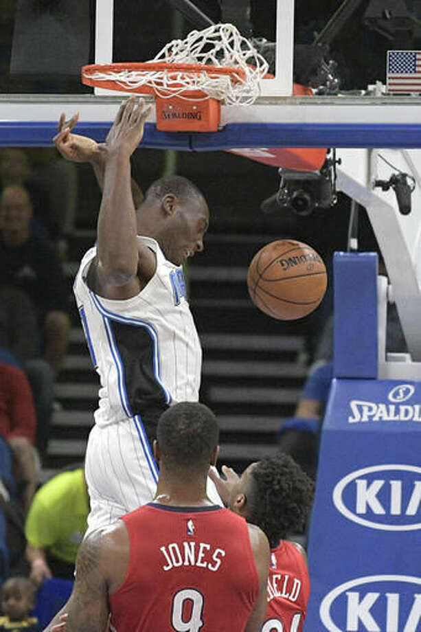Orlando Magic forward Bismack Biyombo dunks the ball over New Orleans Pelicans forward Terrence Jones (9) and Buddy Gield (24) during the first half of an NBA basketball game in Orlando, Fla., Wednesday, Nov. 16, 2016. (AP Photo/Phelan M. Ebenhack)