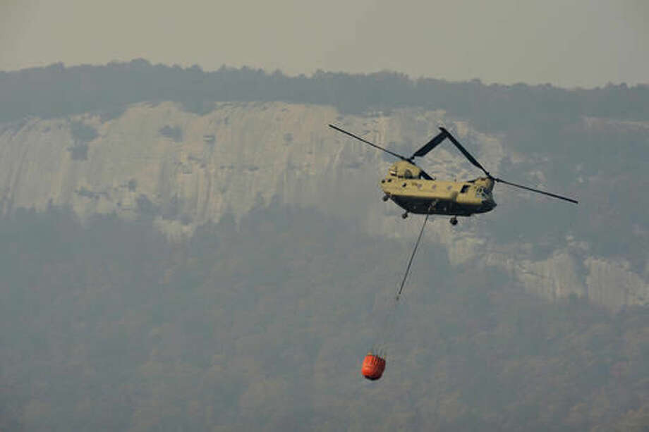 In this Tuesday, Nov. 15, 2016 photo, a Chinook carrying water travels over Table Rock State Park in S.C., as firefighters continue to battle wildfires. (Heidi Heilbrunn/The Greenville News via AP)
