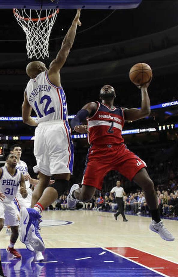 Washington Wizards' John Wall, right, goes up for a shot against Philadelphia 76ers' Gerald Henderson during the second half of an NBA basketball game, Wednesday, Nov. 16, 2016, in Philadelphia. Philadelphia won 109-102. (AP Photo/Matt Slocum)