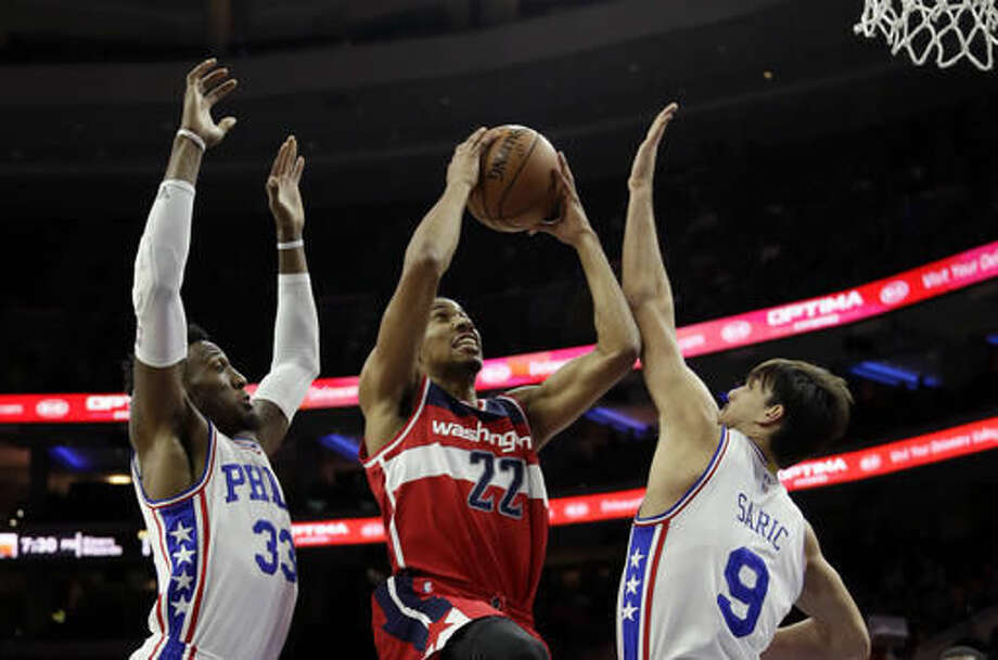 Washington Wizards' Otto Porter Jr., center, goes up for a shot between Philadelphia 76ers' Dario Saric, right, and Robert Covington during the first half of an NBA basketball game, Wednesday, Nov. 16, 2016, in Philadelphia. (AP Photo/Matt Slocum)