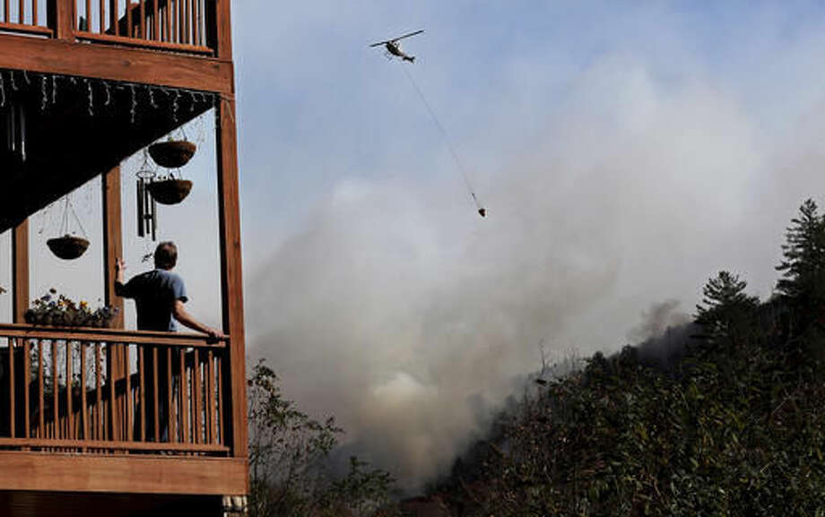 Eric Willey looks on from the porch of his home as a helicopter works on dropping water on the approaching Rock Mountain wildfire, Wednesday, Nov. 16, 2016, in Tate City, Ga. Residents are under a pre-evacuation order as firefighters work to keep the fire away from their homes. (Curtis Compton/Atlanta Journal-Constitution via AP)