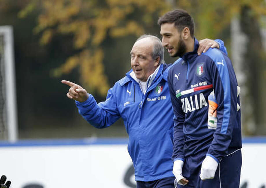 Italian soccer team coach Giampiero Ventura, left, hugs goalkeeper Gianluigi Donnarumma during a training session in Milan, Italy, Monday, Nov. 14, 2016 ahead of the friendly soccer match between Italy and Germany scheduled for Tuesday, Nov. 15, 2016. (AP Photo/ Luca Bruno)