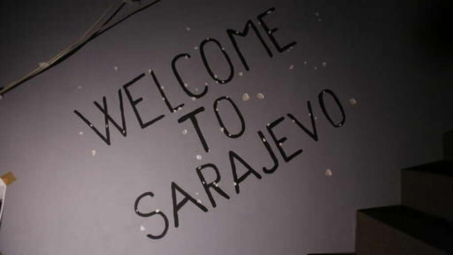 """In this Nov. 12, 2016 photo, """"Welcome to Sarajevo"""" graffiti is seen on a bullet-raked wall of the War Hostel in Sarajevo that offers visitors a unique opportunity to live like civilians in a war zone. Hostel guests must do without electricity, running water and heating, but have the luxury of knowing they won't be killed, starved or lose family or friends. (AP Photo/Amel Emric)"""