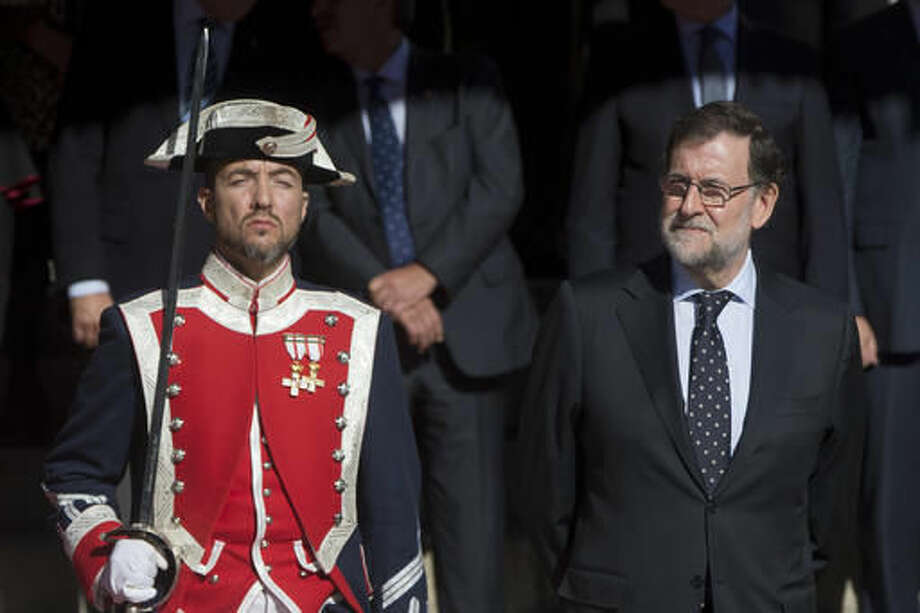 Spain's Prime Minister Mariano Rajoy stands by an honour guard after the new opening session of the Spanish parliament in Madrid, Spain, Thursday, Nov. 17, 2016. Spain's Prime Minister Mariano Rajoy will begin a second term in office, this time with a minority government after a parliamentary vote ended a 10-month political deadlock following two inconclusive elections. (AP Photo/Paul White)