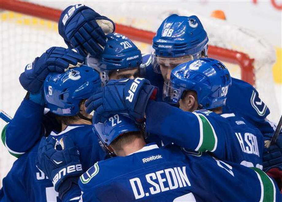 Vancouver Canucks' Luca Sbisa, left, of Italy; Daniel Sedin (22), of Sweden; Brandon Sutter; Nikita Tryamkin (88), of Russia; and Henrik Sedin, of Sweden, celebrate Sutter's goal against the New York Rangers during the second period of an NHL hockey game Tuesday, Nov. 15, 2016, in Vancouver, British Columbia. (Darryl Dyck/The Canadian Press via AP)
