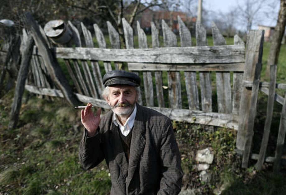An elderly man smokes on the street in the village of Adzince, about 250 kilometers (150 miles) south of Belgrade, Serbia, Wednesday, Nov. 16, 2016. Residents of a remote mountain hamlet in southern Serbia admire Vladimir Putin so much that they've decided to rename their village after the Russian president. (AP Photo/Darko Vojinovic)