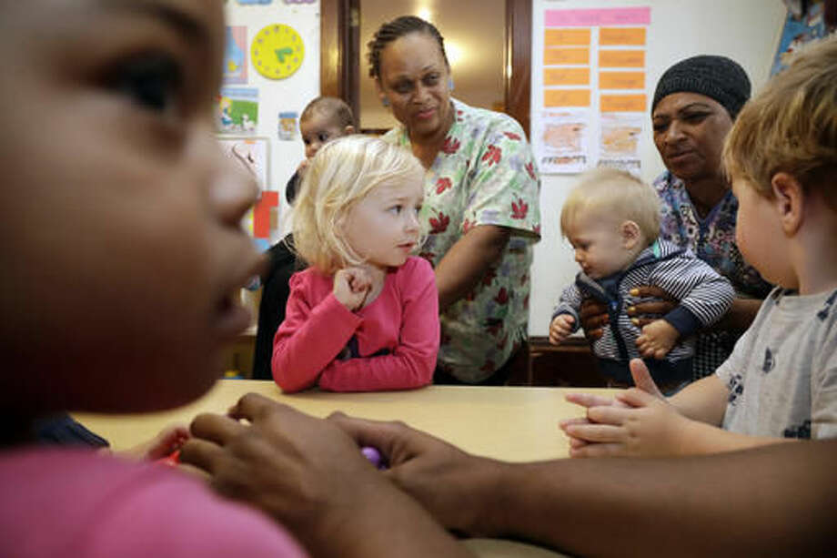 In this Thursday, Oct. 20, 2016, photo, Nancy Harvey, center, owner of Lil' Nancy's Primary Schoolhouse, is surrounded by staff and children she cares for at her home and child care center, in Oakland, Calif. Most U.S. households are heading for a worse lifestyle in retirement than they had while they were working, because they simply aren't saving enough, experts say. Harvey, who has less than $2,000 saved despite her decades of work, plans to continue with real-estate classes in hopes that it can provide a second job.(AP Photo/Marcio Jose Sanchez)