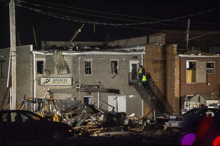 Emergency personnel investigate the damage done from an explosion to Advanced Rehab and Sports Medicine in Canton, Ill., Wednesday, Nov. 16, 2016. Authorities say one person was killed and several people injured in a natural gas explosion in the central Illinois community of Canton. The Peoria Journal Star reported the explosion occurred just before 6 p.m. in a building along First Avenue. Officials say the explosion Wednesday evening occurred near the downtown square and damaged several buildings. (Lewis Marien/The Journal-Star via AP)