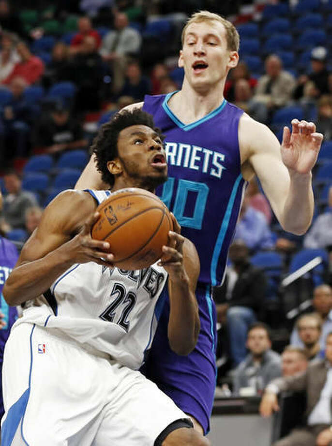 Minnesota Timberwolves' Andrew Wiggins, left, eyes the basket as Charlotte Hornets' Cody Zeller looms over him in the first quarter of an NBA basketball game Tuesday, Nov. 15, 2016, in Minneapolis. (AP Photo/Jim Mone)