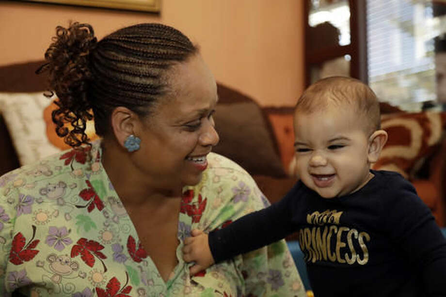 In this Thursday, Oct. 20, 2016, photo, Nancy Harvey, owner of Lil' Nancy's Primary Schoolhouse, left, cares for a toddler at her home, which has she has converted into a child care center, in Oakland, Calif. Most U.S. households are heading for a worse lifestyle in retirement than they had while they were working, because they simply aren't saving enough, experts say. Harvey, who has less than $2,000 saved despite her decades of work, plans to continue with real-estate classes in hopes that it can provide a second job. (AP Photo/Marcio Jose Sanchez)