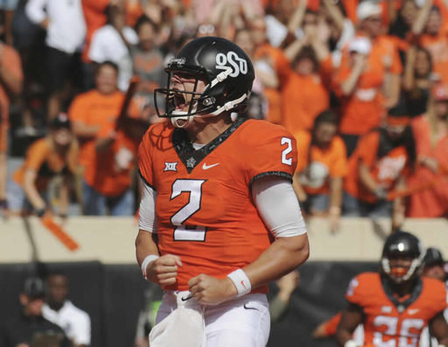 FILE - In this Oct. 29, 2016, file photo, Oklahoma State quarterback Mason Rudolph screams after scoring a touchdown in the third quarter of an NCAA college football game against West Virginia, in Stillwater, Okla. After escaping with a 45-44 victory over Texas Tech on Saturday, No. 13 Oklahoma State needs to win next week against TCU to set up a showdown with No. 8 Oklahoma on Dec. 3 for the Big 12 championship, with a chance at the College Football Playoff still a long shot. (AP Photo/Brody Schmidt, File)