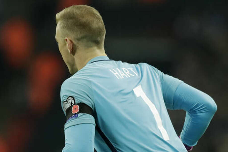 England's goalkeeper Joe Hart wears a black armband with a poppy to mark Armistice Day during the World Cup group F qualifying soccer match between England and Scotland at the Wembley stadium, London, Friday, Nov. 11, 2016. (AP Photo/Matt Dunham)