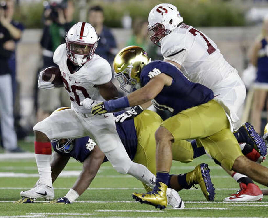 FILE - In this Oct. 15, 2016, file photo, Notre Dame linebacker James Onwualu (17) tackles Stanford running back Bryce Love (20) during the first quarter of an NCAA college football game in South Bend, Ind. It's been quite a journey for Onwualu going from struggling with confidence when he moved from wide receiver to defense after starting four games as a freshman at Notre Dame to helping to turn around a defense that was foundering at the start of the season. (AP Photo/Michael Conroy, File)