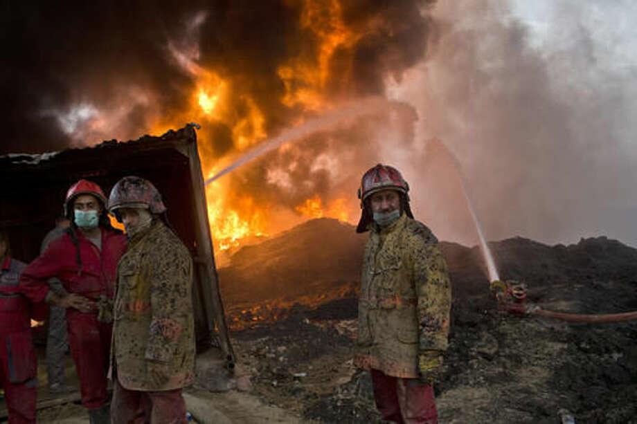 FILE - In this Wednesday, Nov. 9, 2016 file photo, firefighters work at the site of an oil well fire in Qayara, some 31 miles (50 km) south of Mosul, Iraq. As the operation to retake Mosul enters its second month Iraqi forces are preparing for prolonged, grueling urban combat as they slow the tempo of their operation, advancing just a few hundred meters at a time. The individual tactics employed by IS mirror past fights with the group, but the sheer scale of IS defenses and counterattacks in Mosul has overwhelmed Iraq's military.(AP Photo/Marko Drobnjakovic, File)