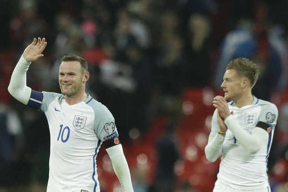 England's Wayne Rooney, left, and England's Jamie Vardy, cheer after winning the World Cup group F qualifying soccer match between England and Scotland with a 3-0 score at the Wembley stadium, London, Friday, Nov. 11, 2016. (AP Photo/Matt Dunham)