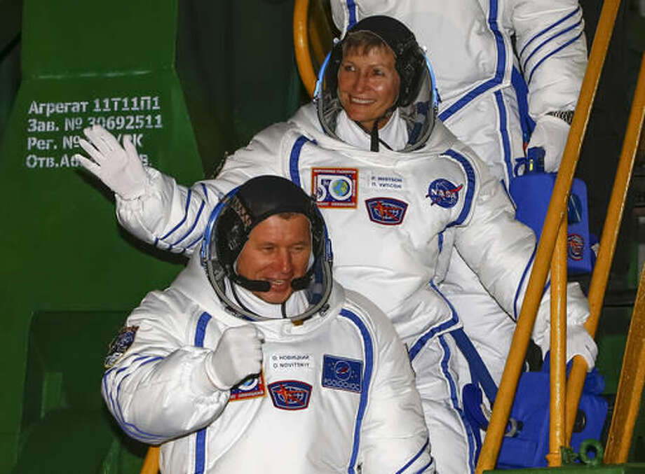 Russian cosmonaut Oleg Novitsky, bottom, and U.S. astronaut Peggy Whitson, crew members of the mission to the International Space Station, ISS, wave near the rocket prior the launch of Soyuz-FG rocket at the Russian leased Baikonur cosmodrome, Kazakhstan, Thursday, Nov. 17, 2016. (AP Photo/Shamil Zhumatov, Pool)