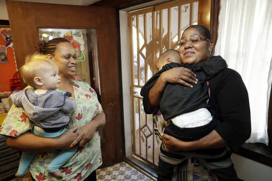 In this Thursday, Oct. 20, 2016, photo, Nancy Harvey, left, owner of Lil' Nancy's Primary Schoolhouse, chats with one her clients, Tamara Purifoy, as she picks up her son Alonzo Simpson, 3, at Harvey's home and child care center, in Oakland, Calif. Most U.S. households are heading for a worse lifestyle in retirement than they had while they were working, because they simply aren't saving enough, experts say. Harvey, who has less than $2,000 saved despite her decades of work, plans to continue with real-estate classes in hopes that it can provide a second job.(AP Photo/Marcio Jose Sanchez)