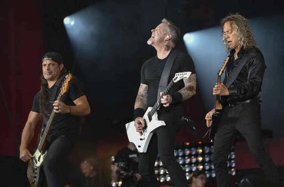 """FILE - In this Sept. 24, 2016, file photo, musicians Robert Trujillo, left, James Hetfield and Kirk Hammett of Metallica perform at the 2016 Global Citizen Festival in Central Park in New York. Metallica joined Jimmy Fallon and The Roots for a toy instrument rendition of its hit, """"Enter Sandman,"""" in a segment that aired on """"The Tonight Show"""" on Nov. 16, 2016. (Photo by Evan Agostini/Invision/AP, File)"""