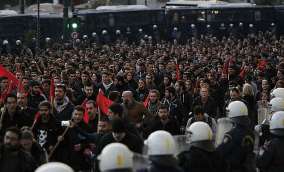 Under the watchful eye of Greek police officers in riot gear, foreground,demonstrators march in central Athens, Thursday, Nov. 17, 2016. Several thousand people march to the U.S. Embassy in Athens under tight police security to commemorate a 1973 student uprising that was crushed by Greece's military junta, that ruled the country from 1967-74. (AP Photo/Thanassis Stavrakis)