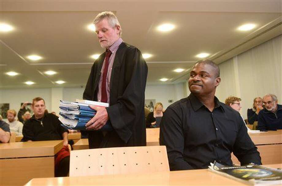 In this Nov. 16, 2016 picture the deserter and former USsoldier Andre Shepherd, right, looks to his lawyer Reinhard Marx, who is carrying documents into the courtroom of the administrative court in Munich, Germany, The court is hearing Shepherd's application for asylum. Shepherd's aylum request was not successful before the European Court in 2015. A Munich court has rejected Thursday Nov. 17, 2016 a U.S. soldier's asylum application in Germany, arguing that he hasn't exhausted all avenues to leave the military. Army Spc. Andre Shepherd deserted from his military base in southern Germany in 2007, claiming he wanted to avoid returning to Iraq where he feared being involved in war crimes. (Tobias Hase/dpa via AP)