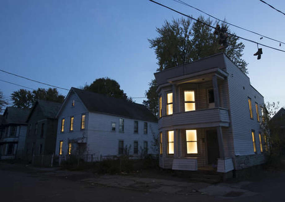 In this Tuesday, Nov. 1, 2016 photo, windows in vacant houses are illuminated with LED lights in Schenectady, N.Y. Windows in more than 150 abandoned buildings in three upstate New York cities have been fitted with light-emitting diodes that steadily brighten and fade, giving the effect of slow breathing. The two-month public art project provides something pretty for gritty neighborhoods of Albany, Schenectady and Troy. (AP Photo/Mike Groll)