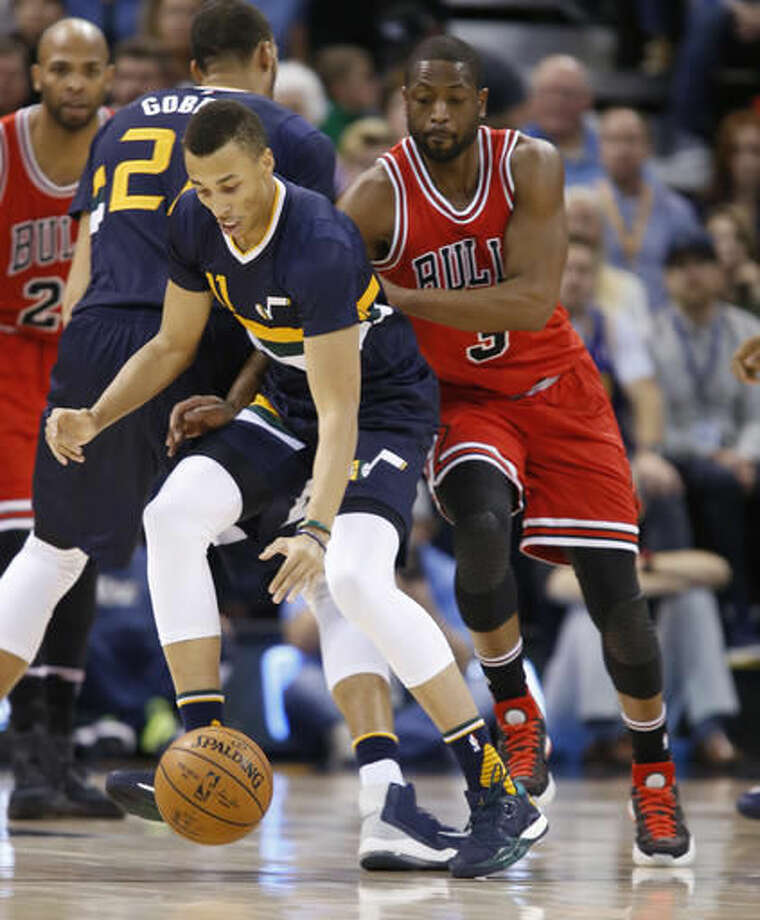 Chicago Bulls guard Dwyane Wade, right, knocks the ball away from Utah Jazz guard Dante Exum, left, during the first half at an NBA basketball game Thursday, Nov. 17, 2016, in Salt Lake City. (AP Photo/George Frey)