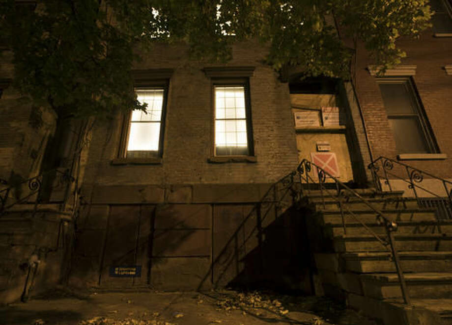 In this Friday, Oct. 28, 2016 photo, windows in a vacant house are illuminated with LED lights in Albany, N.Y. Windows in more than 150 abandoned buildings in three upstate New York cities have been fitted with light-emitting diodes that steadily brighten and fade, giving the effect of slow breathing. The two-month public art project provides something pretty for gritty neighborhoods of Albany, Schenectady and Troy. (AP Photo/Mike Groll)