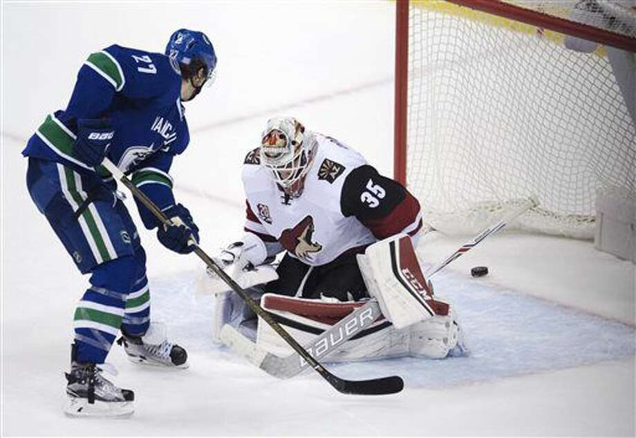 Vancouver Canucks defenseman Ben Hutton (27) scores the game-winning goal past Arizona Coyotes goalie Louis Domingue (35) during overtime of an NHL hockey game Thursday, Nov. 17, 2016, in Vancouver, British Columbia. Vancouver won 3-2. (Jonathan Hayward/The Canadian Press via AP)